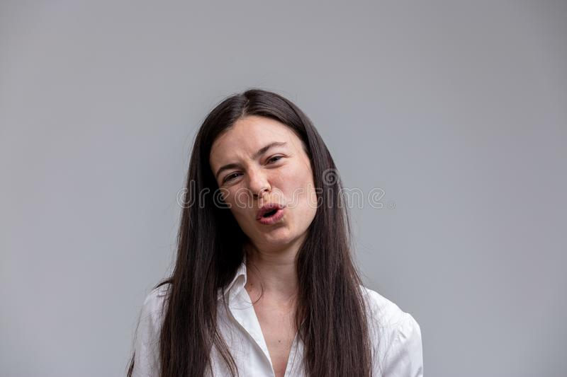 Scornful attractive woman talking to the camera. As she jeers at the viewer with a derisory expression and frown over grey with copy space stock photo