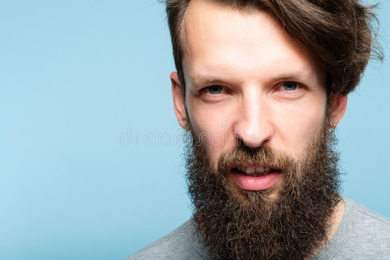 Scornful disdainful disrespectful look man emotion. Man with a scornful disdainful disrespectful look. portrait of a young bearded guy on blue background stock photography