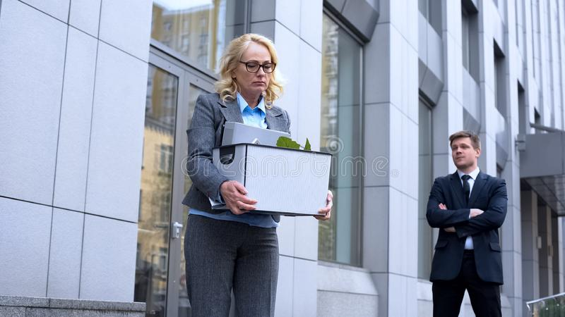 Scornful male employee looking at sad dismissed business woman, work failure royalty free stock photography