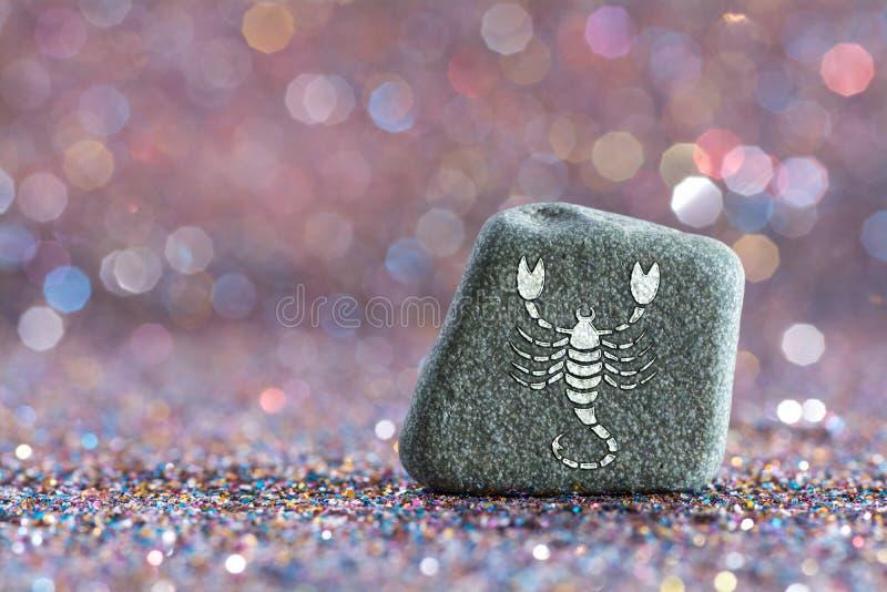 Scorpio zodiac sign. A green stone with Scorpio zodiac sign on glitter boke light background royalty free stock photography