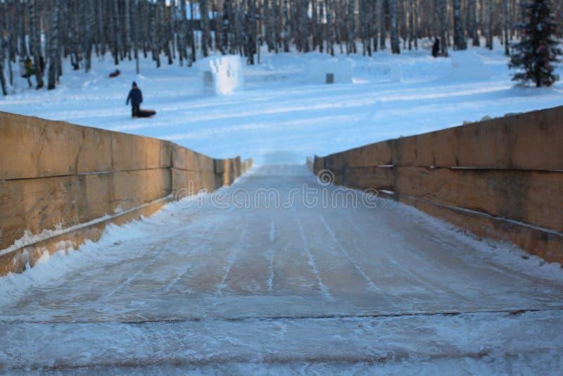 Scorrevole di legno alto del ghiaccio con il pendio ripido ed il piano di scorrimento congelato ghiacciato immagini stock