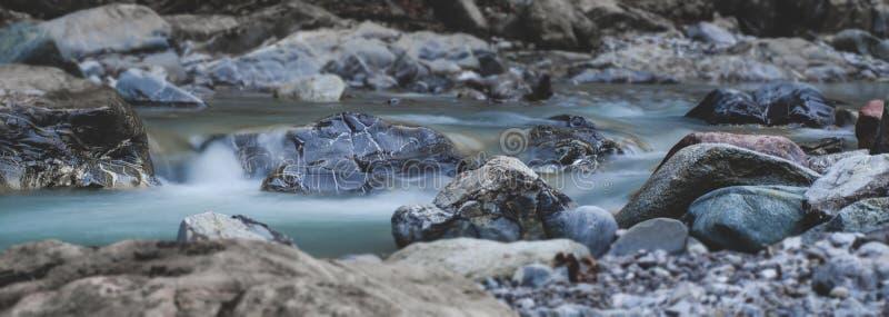 Scorrimenti dell'acqua del fiume sopra le pietre fotografie stock libere da diritti