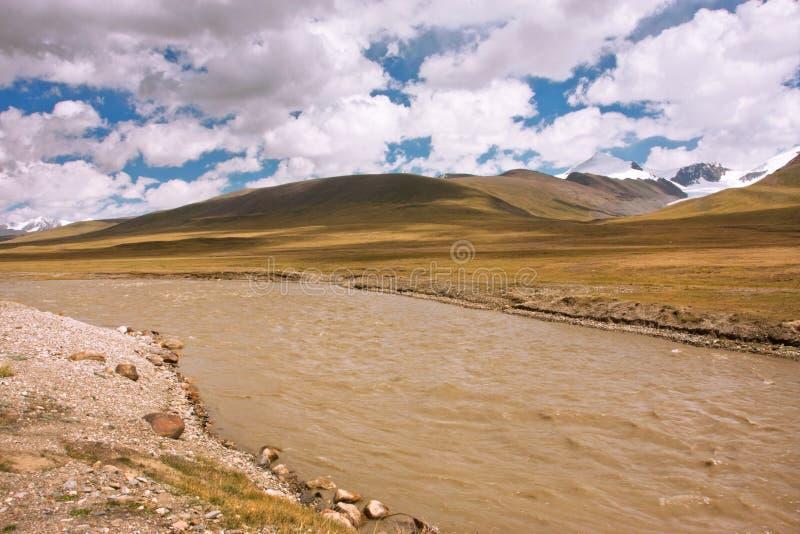 Scorrimenti dell'acqua sporchi da una catena montuosa un giorno soleggiato con le nuvole immagine stock