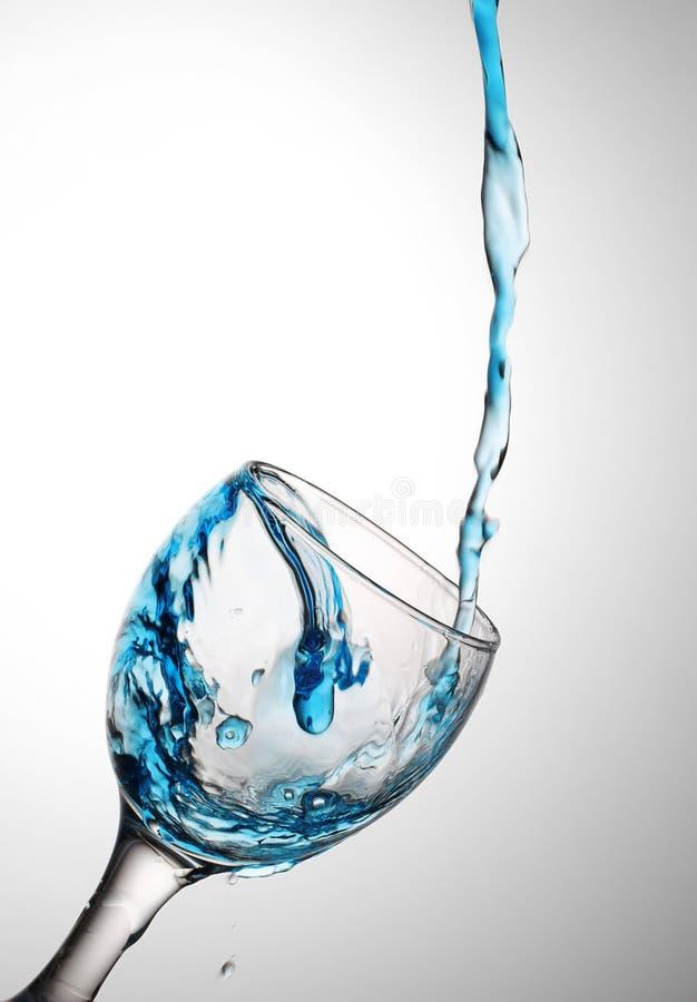Scorrimenti dell'acqua in un vetro immagini stock