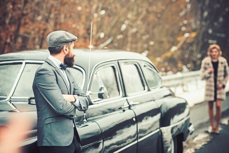 Scorta della ragazza da sicurezza Automobile retro della raccolta e riparazione automatica dall'autista del meccanico Uomo barbut immagini stock libere da diritti