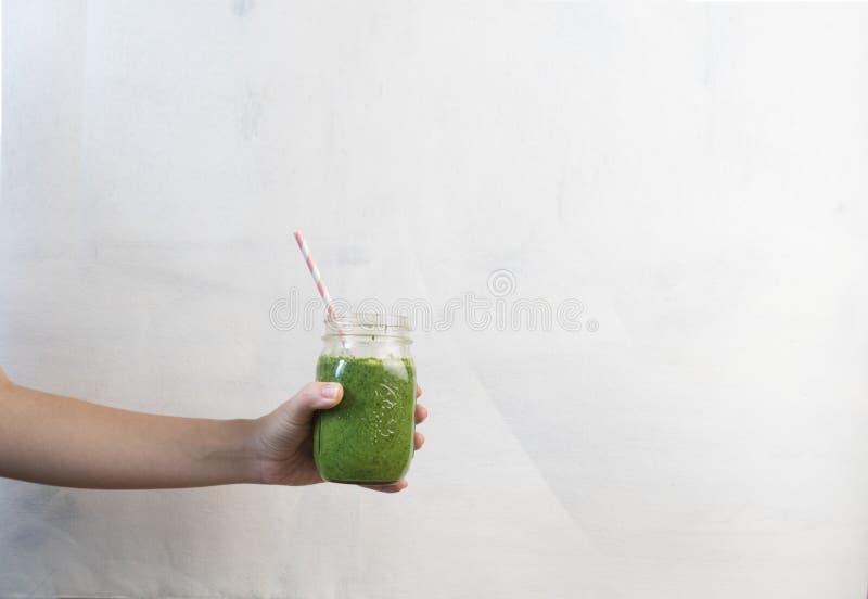 Scossa del frullato della tenuta della mano della donna contro la parete colorata Concetto sano verde bevente del frullato fotografia stock