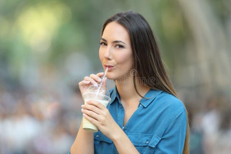 Scossa del latte alimentare della donna nella via che vi esamina fotografie stock libere da diritti