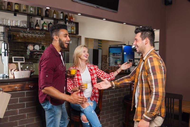Scossa di due uomini della mano di saluto, amici che incontrano tenuta Juice Glasses arancio, sorridere felice immagine stock