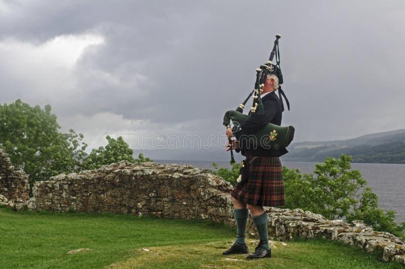 Scot gioca le cornamuse davanti a Loch Ness fotografia stock libera da diritti