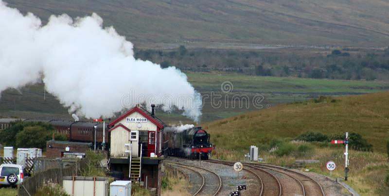 Scots Guardsman steam train at Blea Moor. LMS Royal Scot class preserved steam locomotive Scots Guardsman, number 46115, passing Blea Moor signal box on the royalty free stock photos