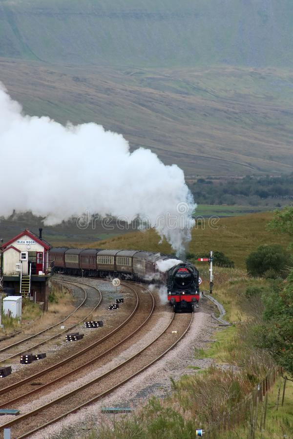 Scots Guardsman steam train at Blea Moor. LMS Royal Scot class preserved steam locomotive Scots Guardsman, number 46115, passing Blea Moor signal box on the royalty free stock photography