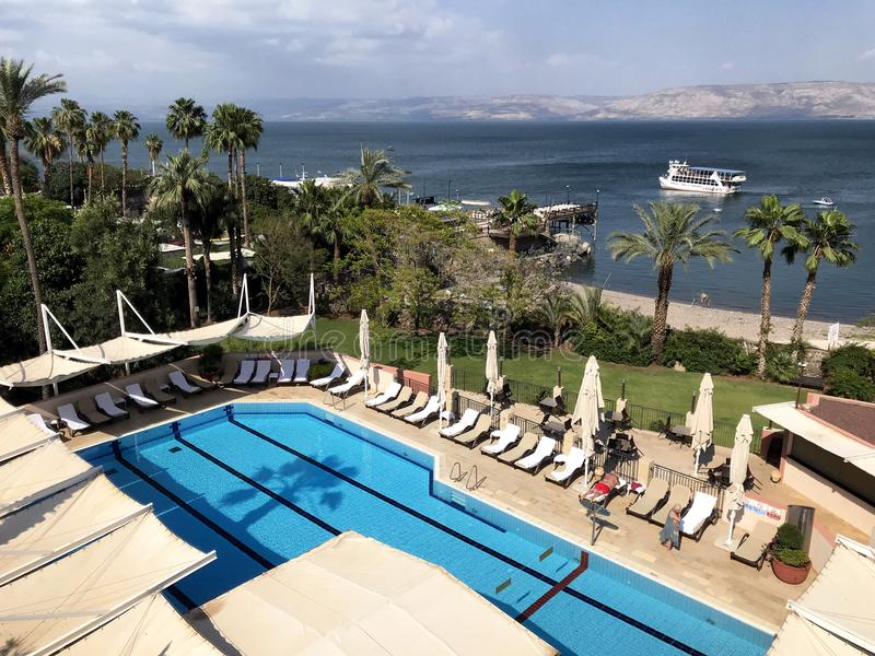 Scots Hotel pool overlooking the Sea of Galilee. TIBERIAS, ISRAEL - MAY 14, 2018: Scots Hotel pool overlooking the Sea of Galilee. The hotel was once the site of stock image