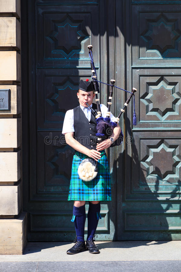 A Scotsman wearing traditional Scottish outfit playing the bagpipes stock photos