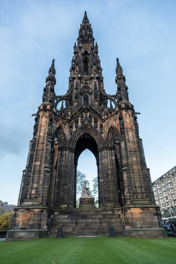 Front view of the Scott Monument in Edinburgh Scotland blue sky and light clouds and fresh clipped green grass at the bottom. Scott Monument in Edinburgh royalty free stock image