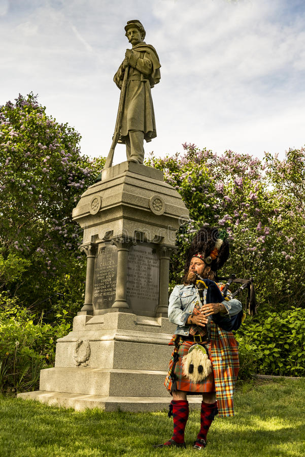 Scottish bagpiper dressed in traditional red and black tartan dress stock image