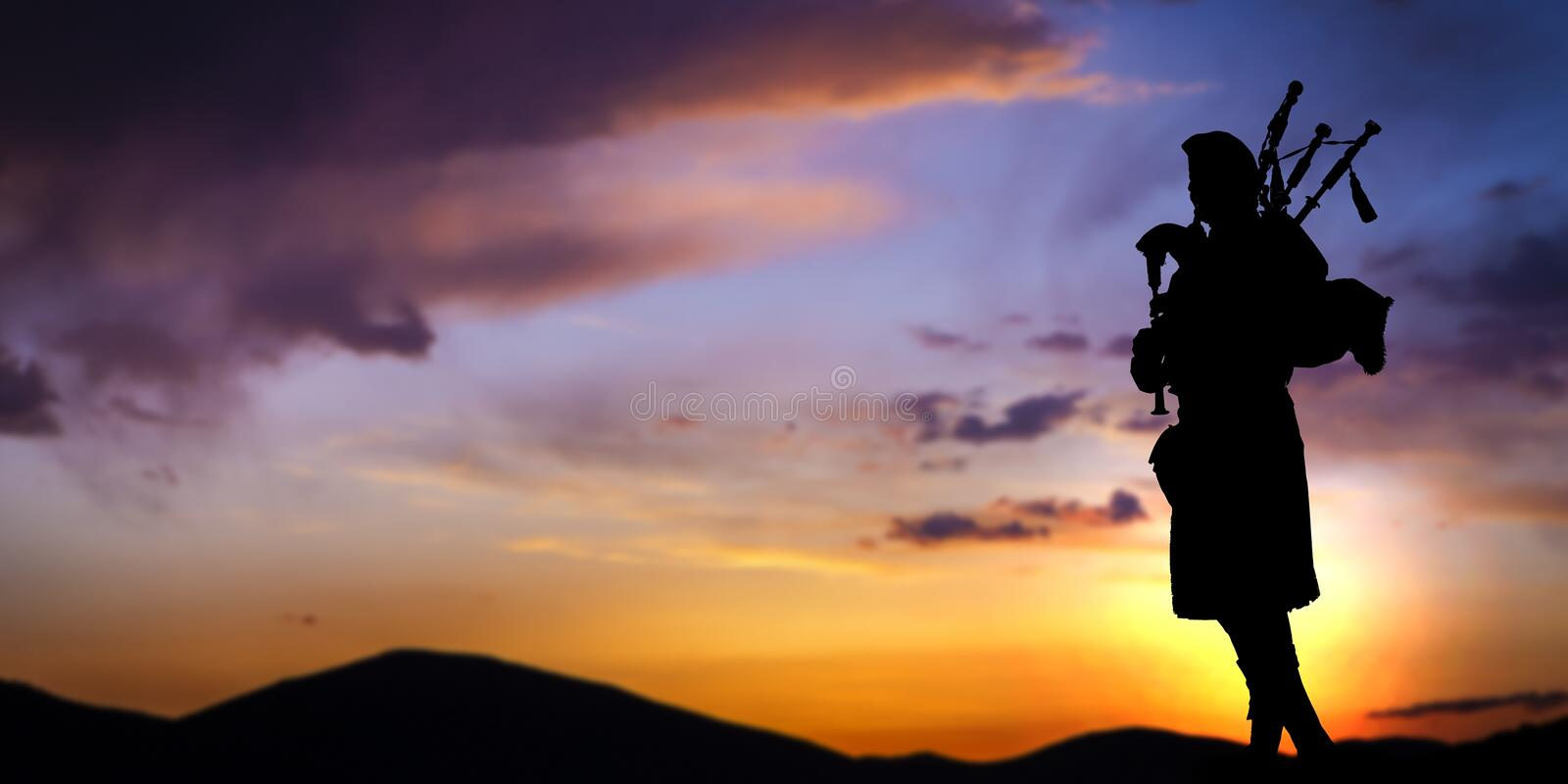 Scottish bagpiper at sunset. A silhouette of a Scottish bagpiper at sunset royalty free stock photos