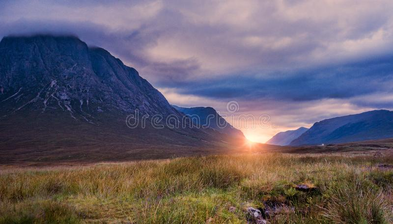 Scottish Highlands near Glencoe, Scotland at sunset after a storm. The sun is peeking out behimd the mountains royalty free stock images