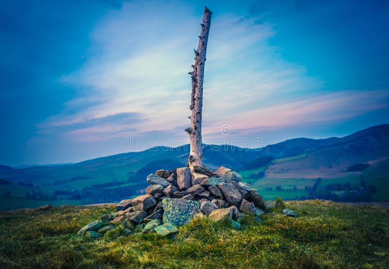 Scottish Hilltop At Sunset. Scottish Hilltop With Cairn And Wooden Post At Sunset stock photos