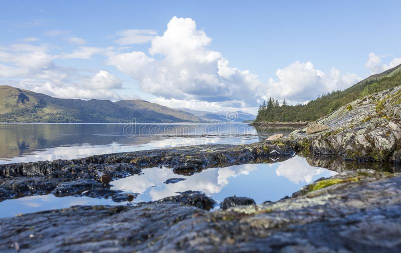 Scottish Loch with reflections. The sky and clouds reflected in the waters of a scottish Loch in the highlands with rocks royalty free stock photos