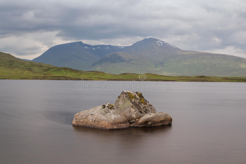 Scottish loch with a stone. In the water and mountains in the background stock images