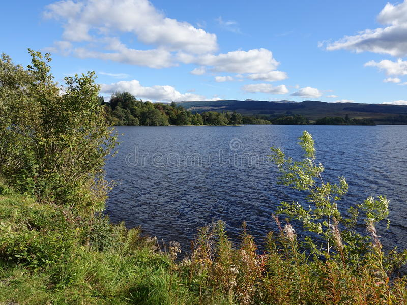 Scottish loch. View of a Scottish loch with blue sky, clouds and hills stock image