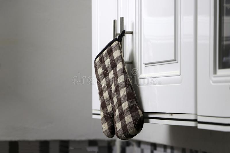 Scottish pattern of heat resistant gloves hanging on the cabinet in the kitchen. Scottish pattern of heat resistant gloves hanging on the white cabinet in the royalty free stock photos