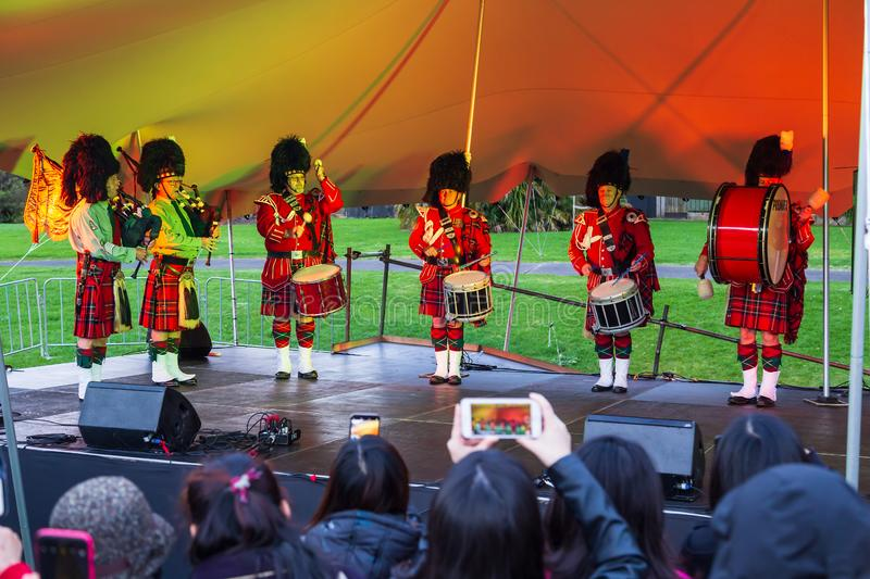 Scottish pipe and drum band performing in front of a crowd royalty free stock photo