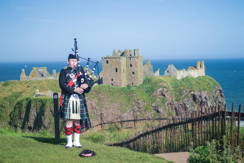 Scottish Piper at Dunnottar Castle. Aberdeenshire, Scotland. He plays pipe with the castle in background stock photos