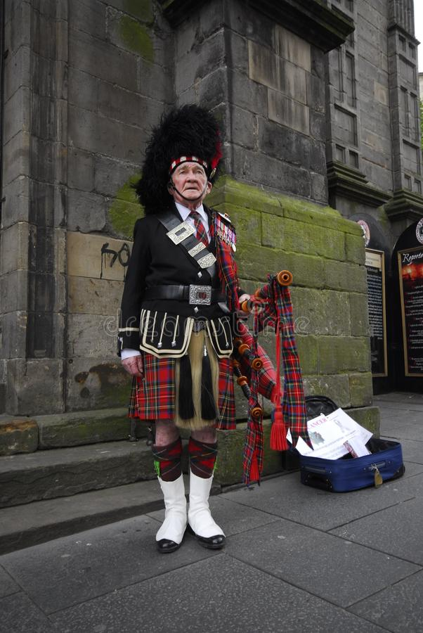 Scottish piper in Edinburgh. Scottish piper with medals standing in an Edinburgh street in full traditional dress including tartan kilt and sporran holding royalty free stock images