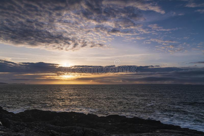 Scottish West Coast Sunset. The sun setting over the Sea of the Hebrides with the Isle of Mull and Coll in the distance, from Ardnamurchan, Scotland stock photography