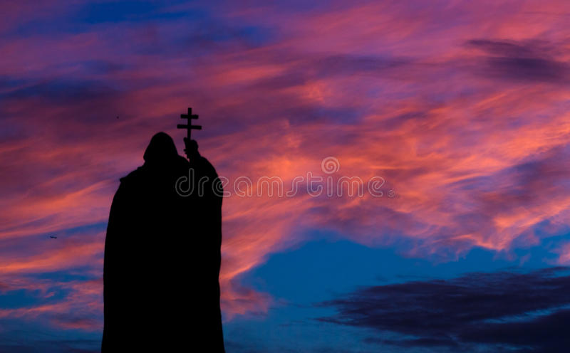 Scourge of God. Monk's silouette under the burning sky royalty free stock photography