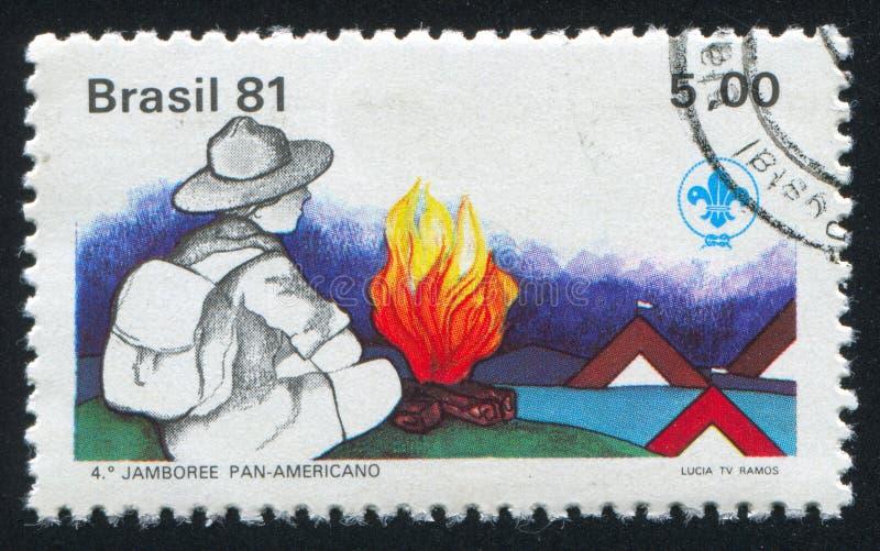 Scout de garçon et feu de camp image stock