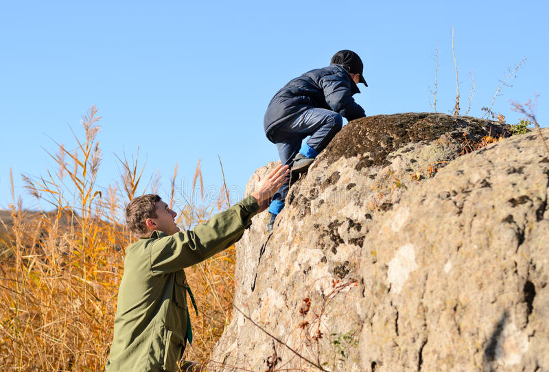 Scout helping a young boy rock climbing royalty free stock images