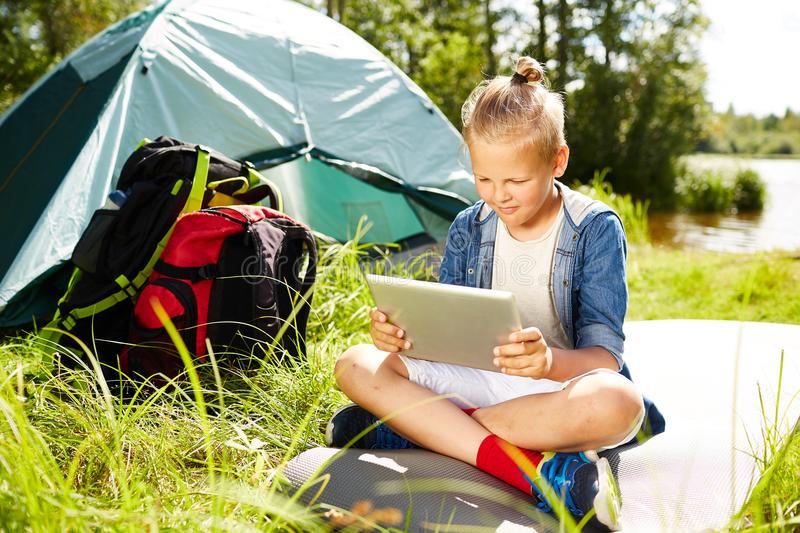 Scout with tablet. Young boy with tablet watching online videos while enjoying trip summer day royalty free stock images
