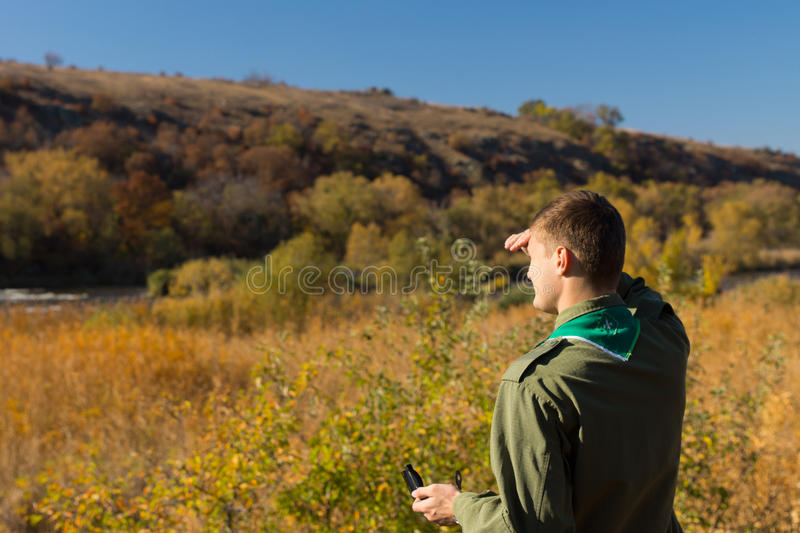 Scout trying to get his bearings. As he stands in the wilderness looking into the sun with a magnetic compass in his hand for navigation stock images