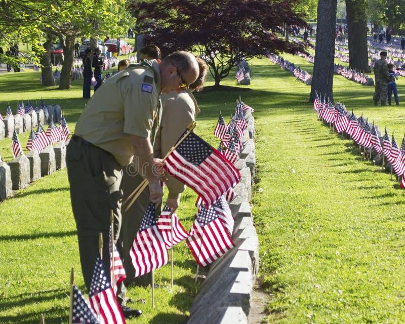 Scoutmaster кладя флаги на военные могилы стоковые изображения rf