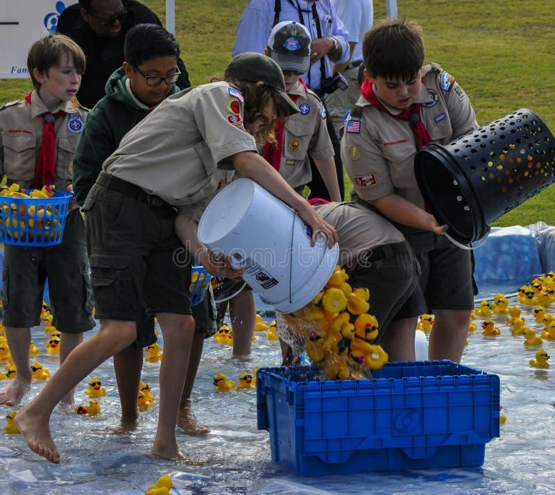 Scouts de fille et de garçon Duckies en caoutchouc de retour dans des caisses à la finition d'une course photographie stock