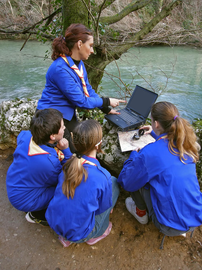 Scouts are oriented with laptop 1. Portrait of a young scouts with teacher (best friends) with laptop, map and compass in nature learning orientation. Vertical stock image