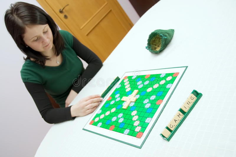 Scrabble. Young white caucasian woman plays scrabble at the table stock image