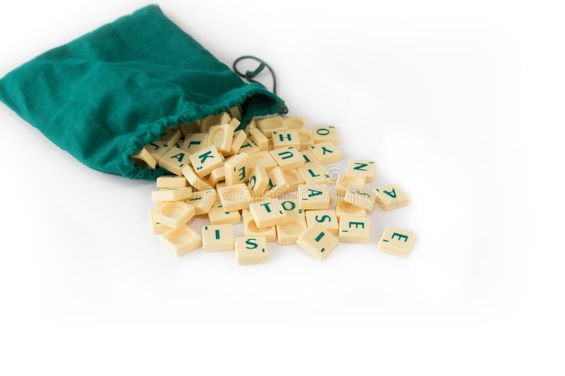 Scrabble tiles and green bag. Random Scrabble game letter tiles with score value coming out of their green drawstring bag, isolated on white background stock photos
