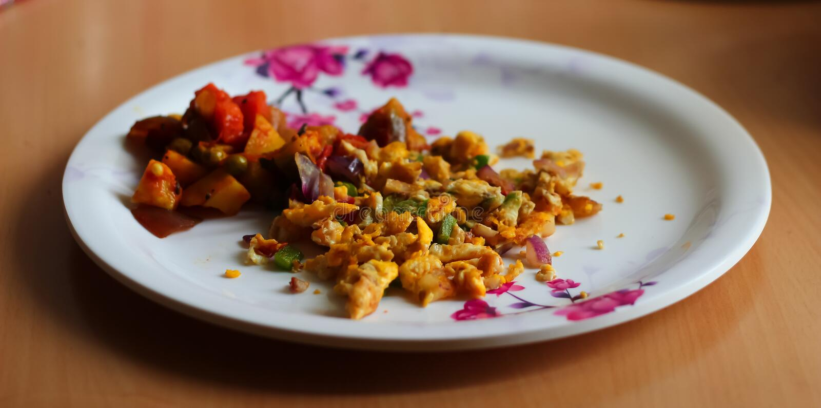 Scrambled egg omlette and mixed vegetable served on a plate. Indian home made dish. side view royalty free stock photos