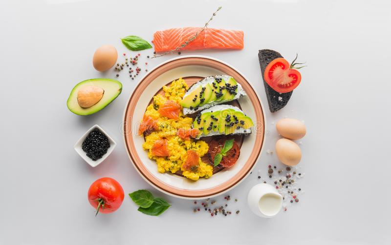 Scrambled egg with salmon fish, bruschetta with avocado stock photos