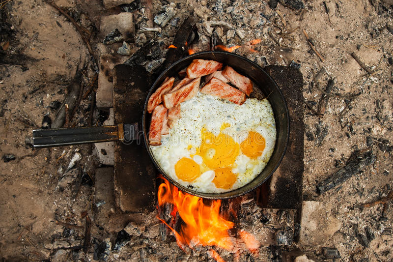 Scrambled eggs with bacon on the cast-iron pan on a bonfire. royalty free stock photo