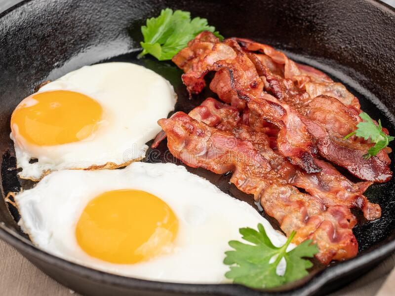 Fried eggs with bacon in a pan royalty free stock photography