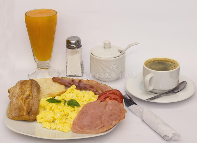 Scrambled eggs, basil, papaya juice, coffee, ham, fried bacon, bread. royalty free stock images