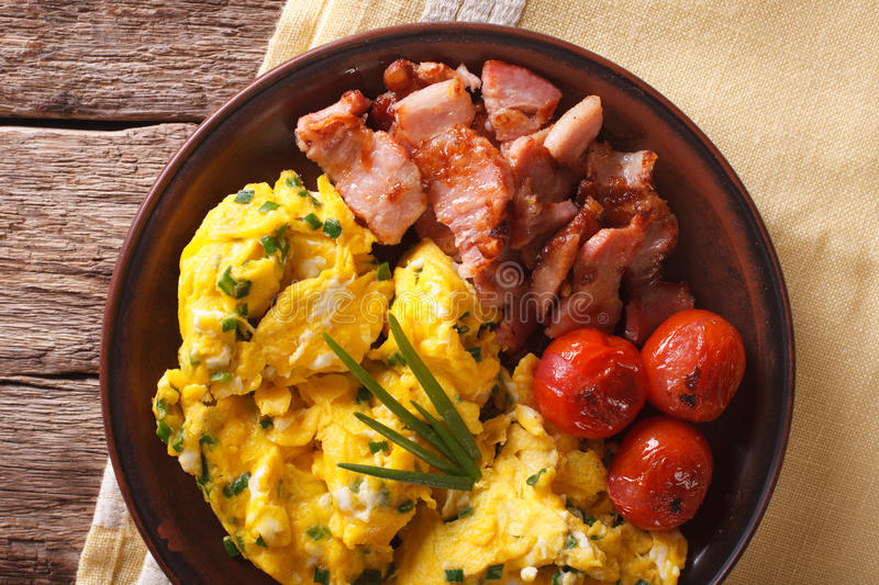 Scrambled eggs with chives, bacon and tomatoes close-up. horizon stock images