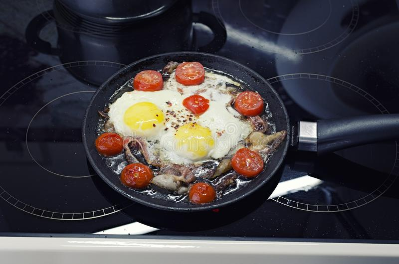 Scrambled eggs cooking in a frying pan, cooking on a ceramic stove, fried eggs with bacon and tomato, top view closeup royalty free stock photo