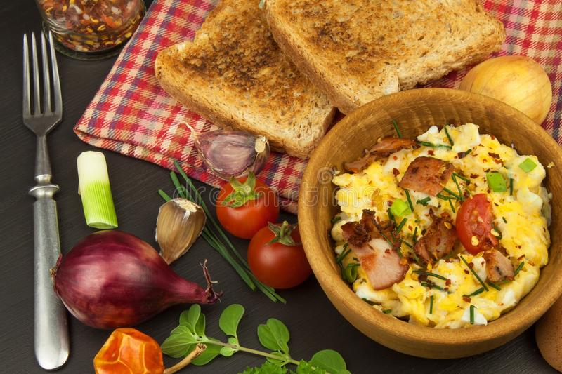 Scrambled eggs with fried bacon. English breakfast. Toast and scrambled eggs with chives. Recipe for a healthy meal stock photos