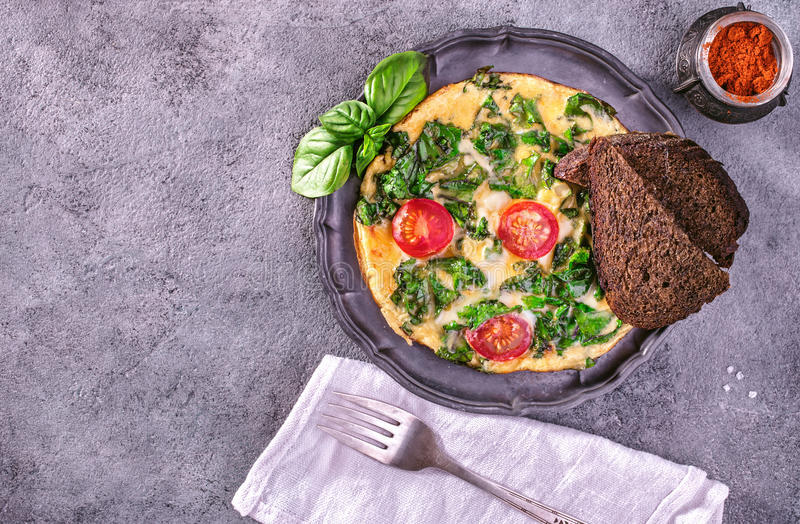 Scrambled eggs with kale. And toast on concrete surface, vintage style. Top view with copy space stock images