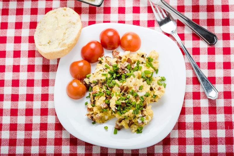 Scrambled eggs with sausage. Tasty breakfast - scrambled eggs with sausage, black coffee and bread with butter stock photography